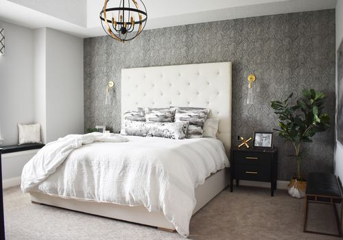 Sophisticated bedroom with large white headboard, wallpapered accent wall