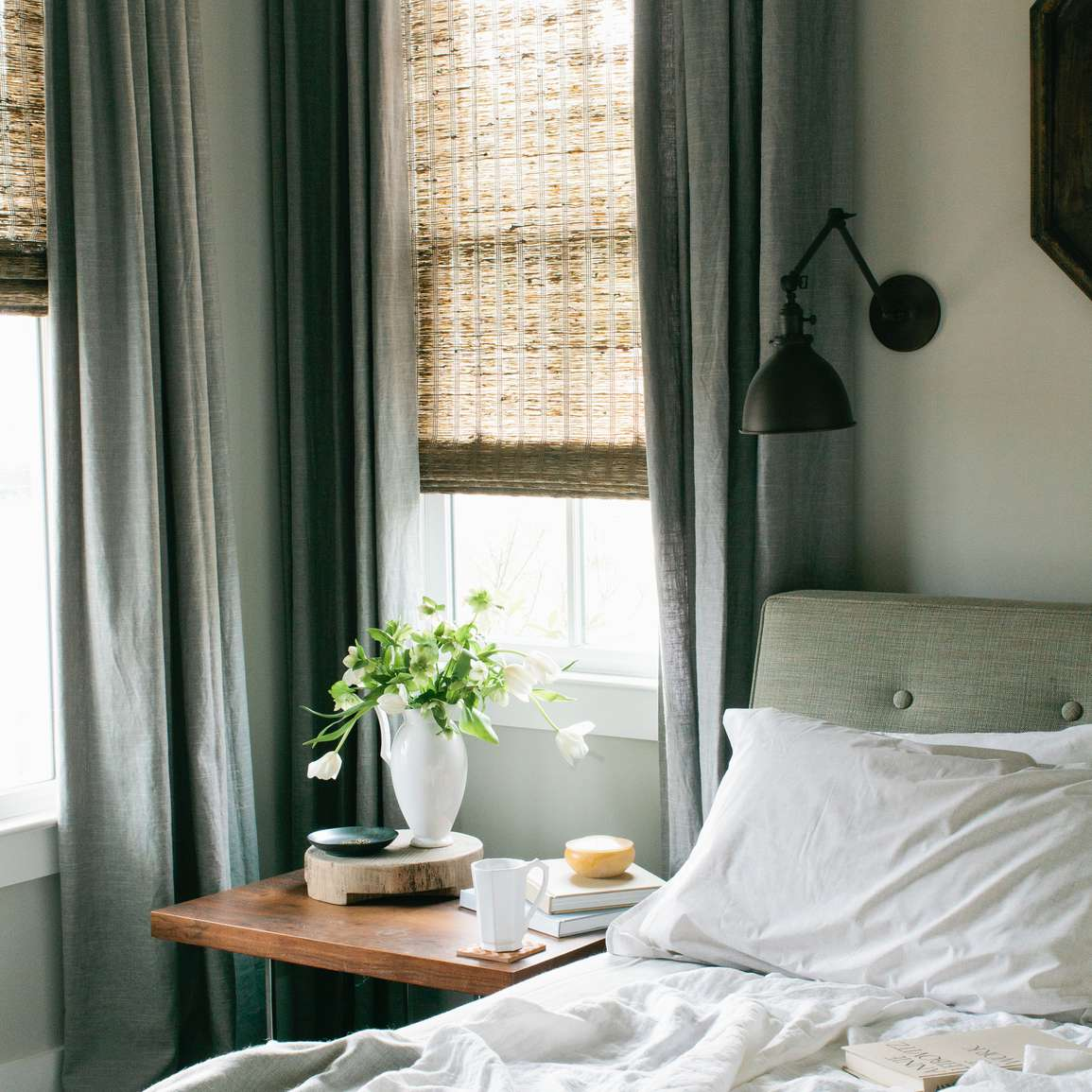 bed with messy sheets next to two windows and a nightstand with a plant and cup of coffee