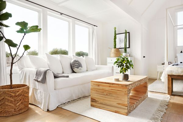 Four post bed and dresser in a beautiful white rustic modern design farmhouse tiny house bedroom with a white linen sofa and cactus on dresser
