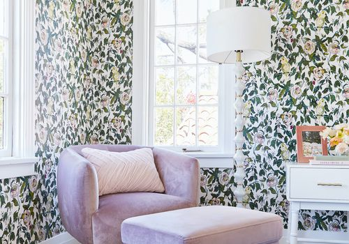 Bedroom with graphic floral wallpaper and purple chair