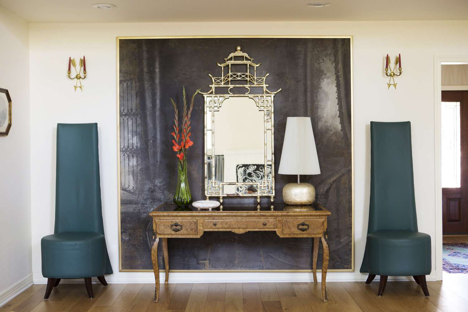 room with two tall decorative teal chairs, oversized artwork serving as backdrop between them. Decorative mirror on desk leaned against artwork