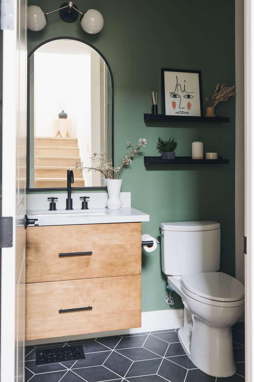 Modern bathroom with floating shelves, green walls