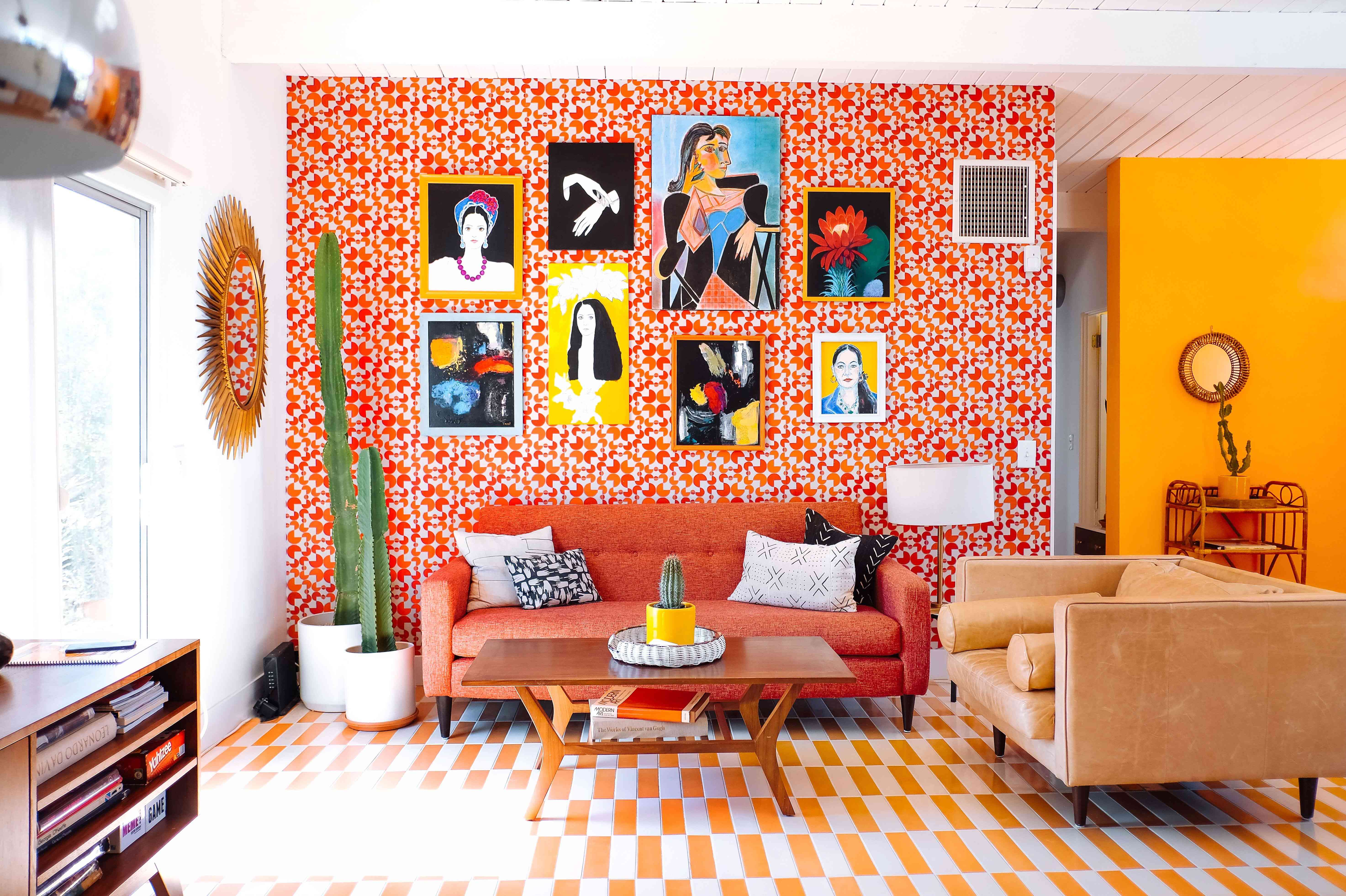 A living room with red printed wallpaper on the walls and a yellow striped rug on the floor