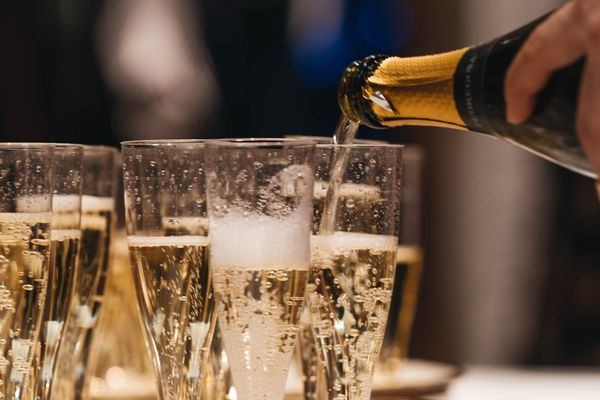 how to open a bottle of champagne - champagne being poured into flutes