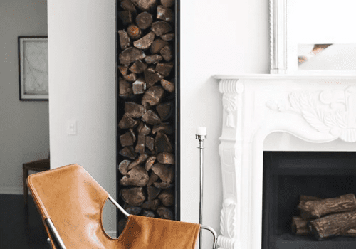 Large mirror rests above mantle with firewood piled in exposed storage in living room