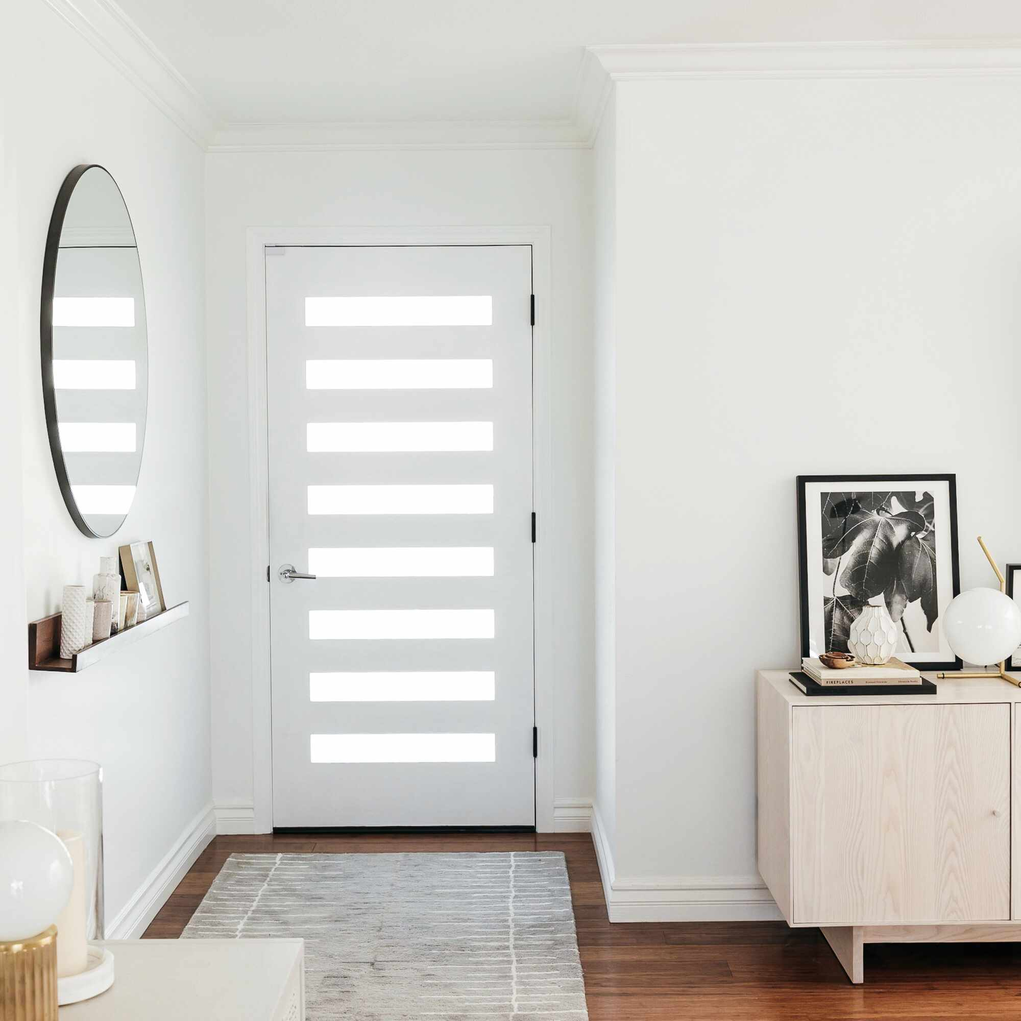 Small entryway with mirror reflecting light from the door