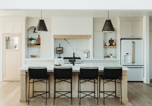 Bright white kitchen with black barstools.