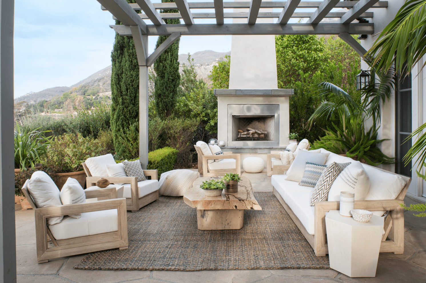 An outdoor fireplace, placed near lots of cozy outdoor seating, a wooden coffee table, and a rug