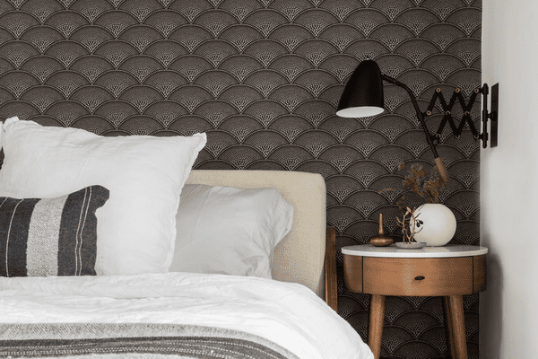 Bedroom with black scalloped wallpapers and white linens.