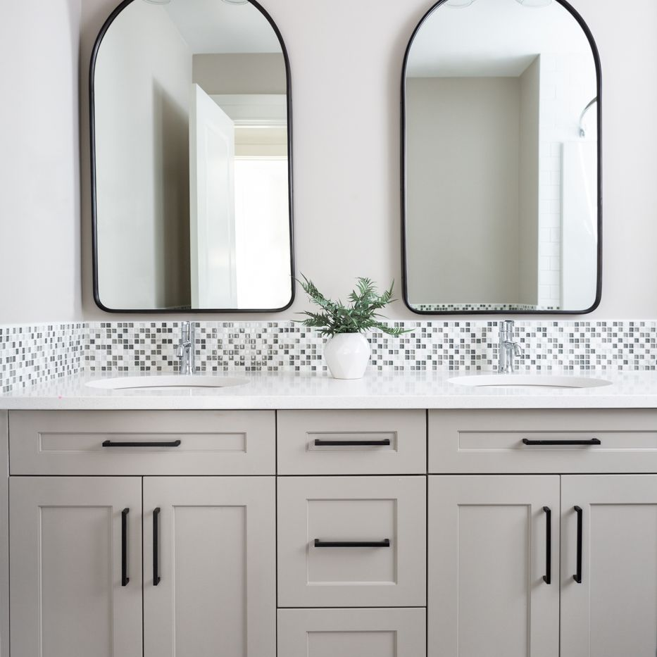 A bathroom with gray cabinets and two mirrors