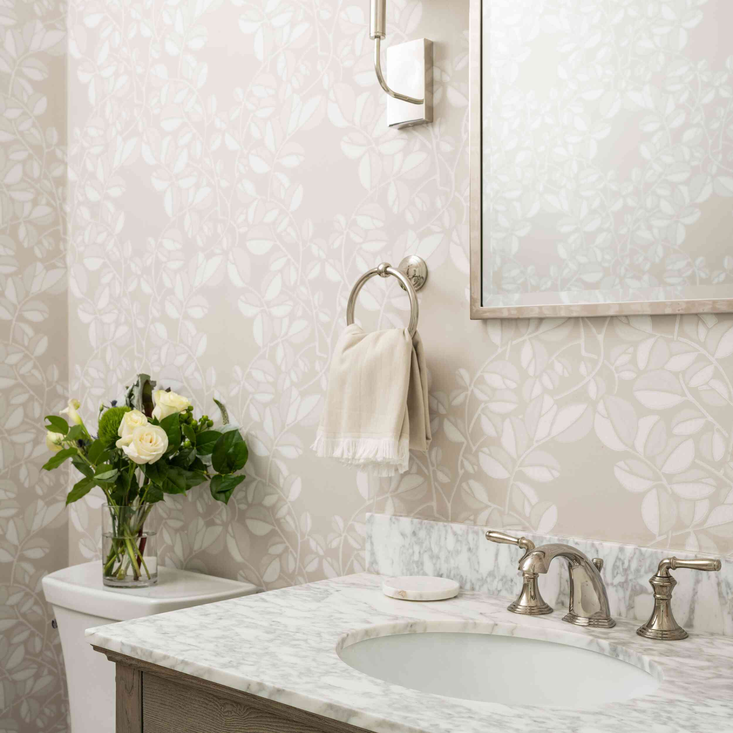 Wallpapered bathroom with marble sink, flower bouquet behind toilet