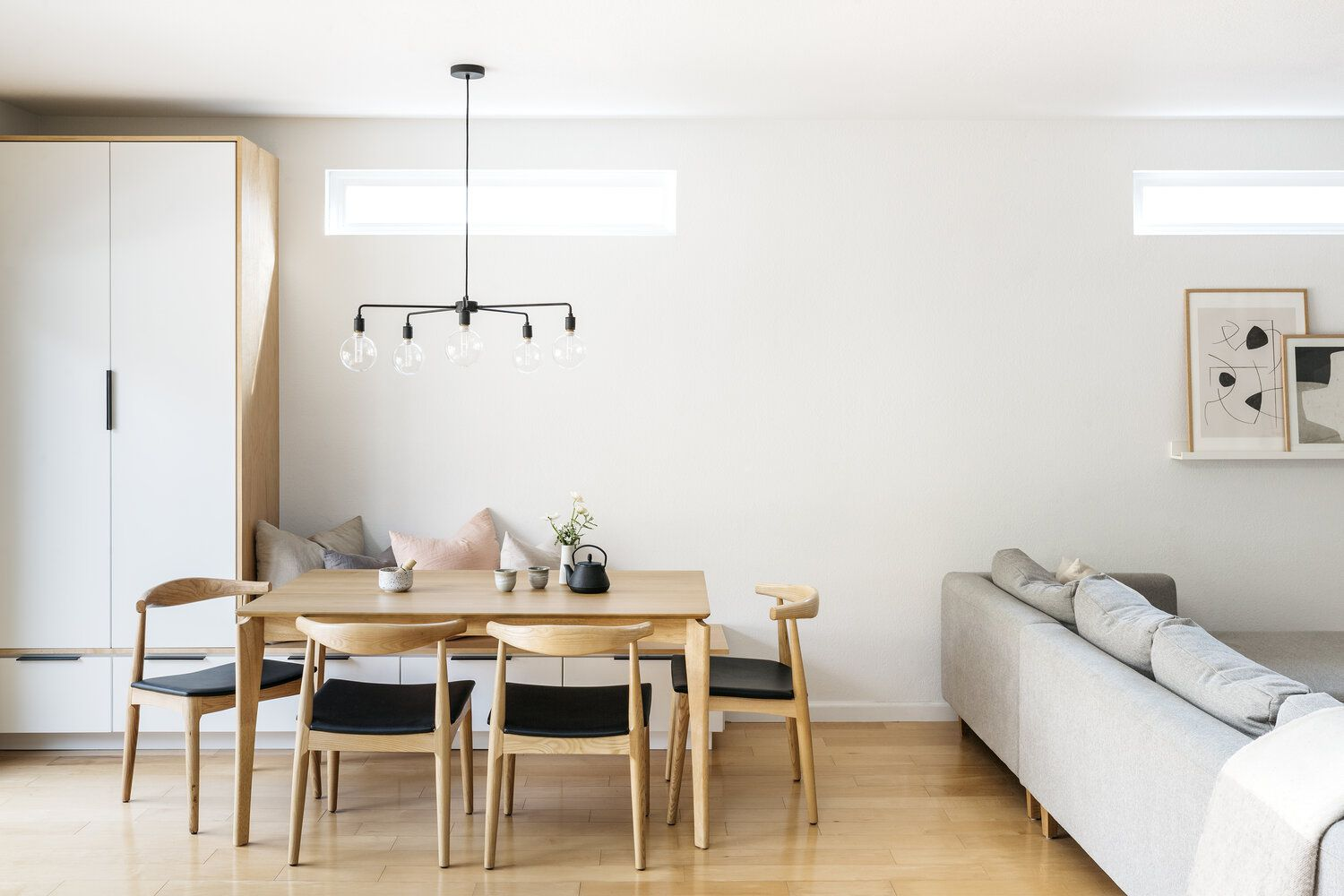 A dining room with sparse decor and a modern lighting fixture