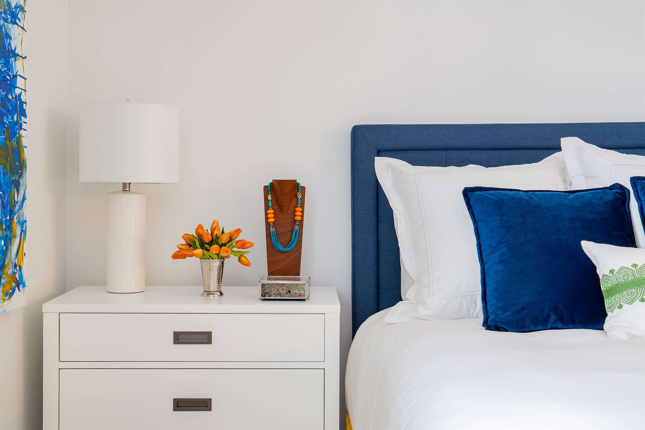 bedside table with orange flowers, modern lamp, and jewelry display