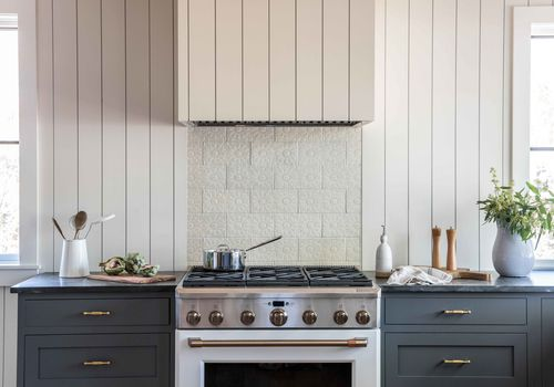A rustic kitchen with a floral-textured backsplash