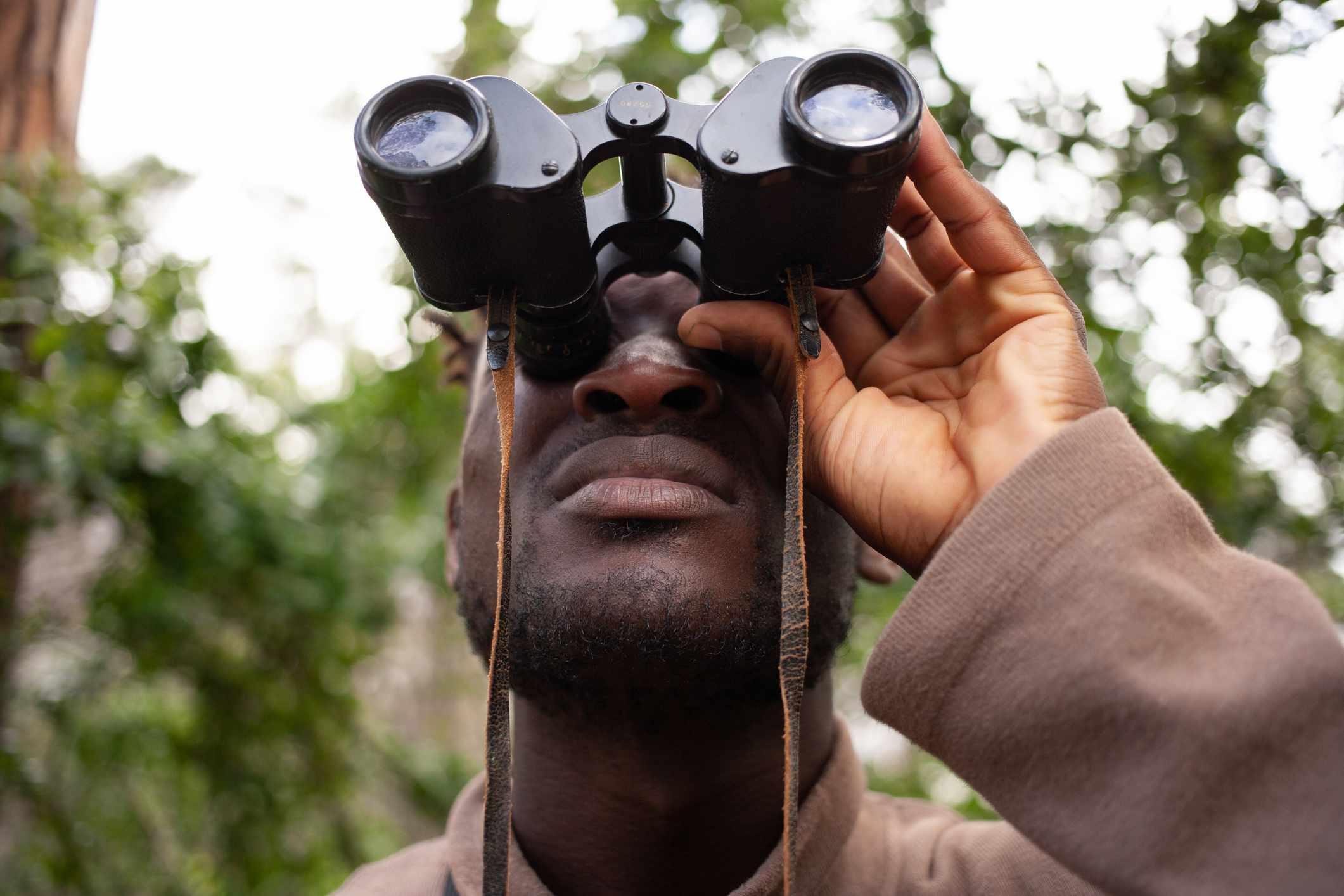 Young man looks through binoculars