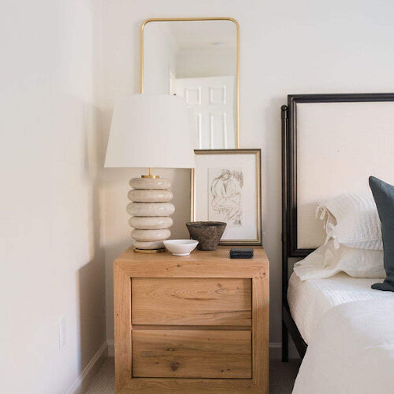 Nightstand with artful decor and lamp.