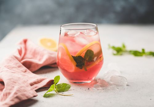 Cocktail in a glass with lemon and mint garnish.