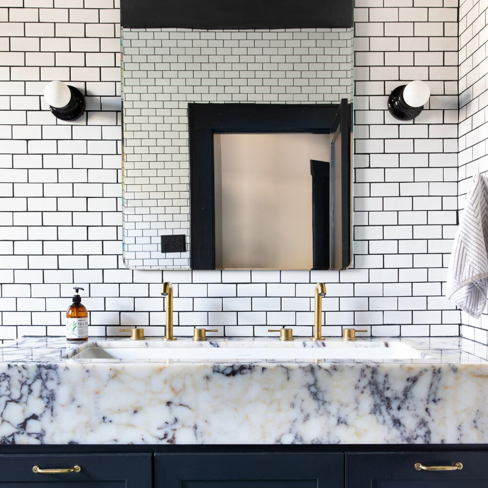 A bathroom backsplash lined with white subway tiles and black grout