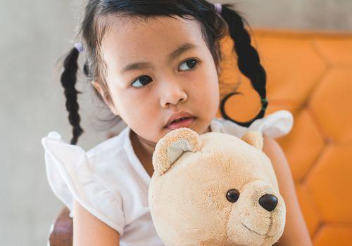 a little girl hugging a teddy bear