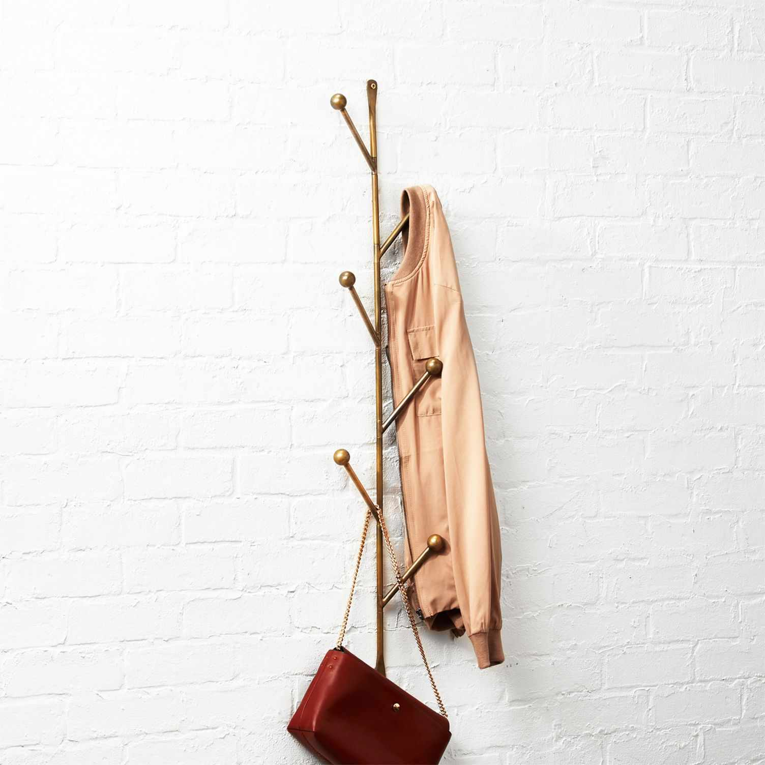 A brass vertical coat rack hanging on the wall with a coat and purse hanging from it.