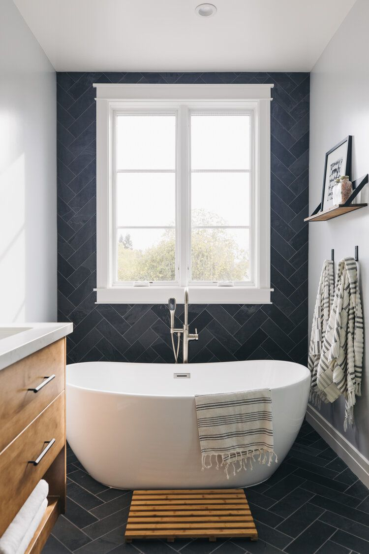 A small primary bathroom with a freestanding tub tucked between tight walls