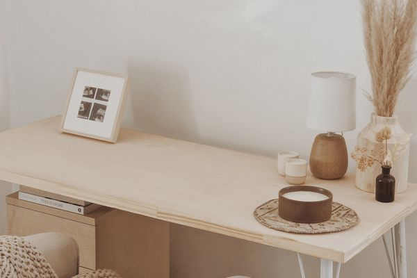 desk area with a dried arrangement and several candles