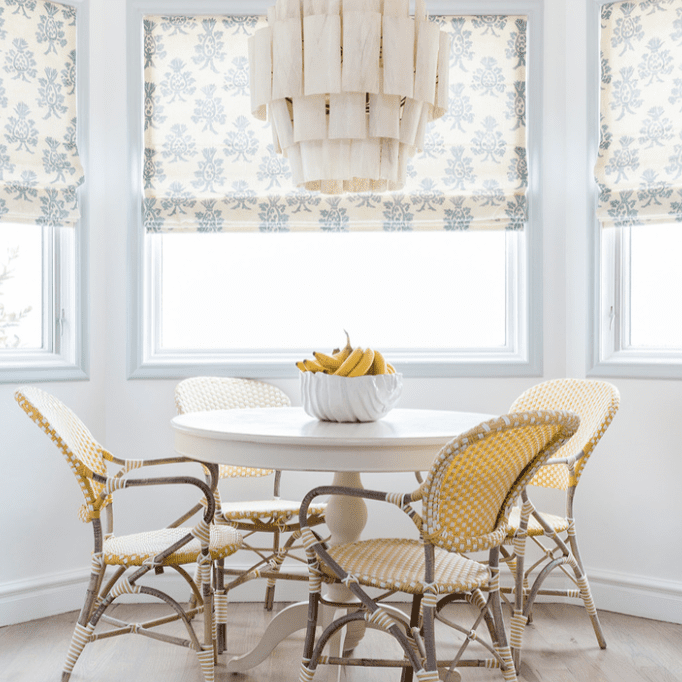 A small dining room table topped with a bowl of bananas