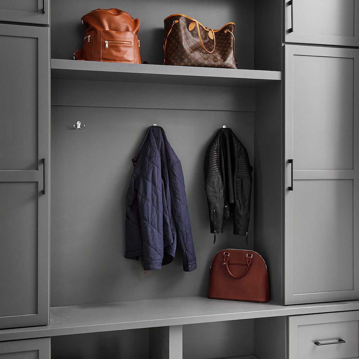 A gray mudroom with several cabinets and shelves