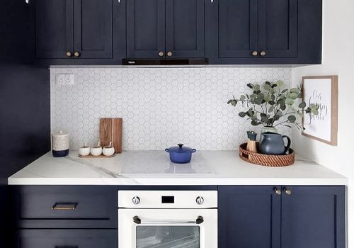 Blue kitchen cabinets with gold hardware.
