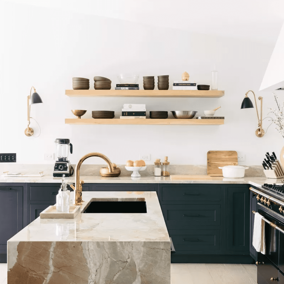A minimalist kitchen with dark green cabinets and a marble kitchen island