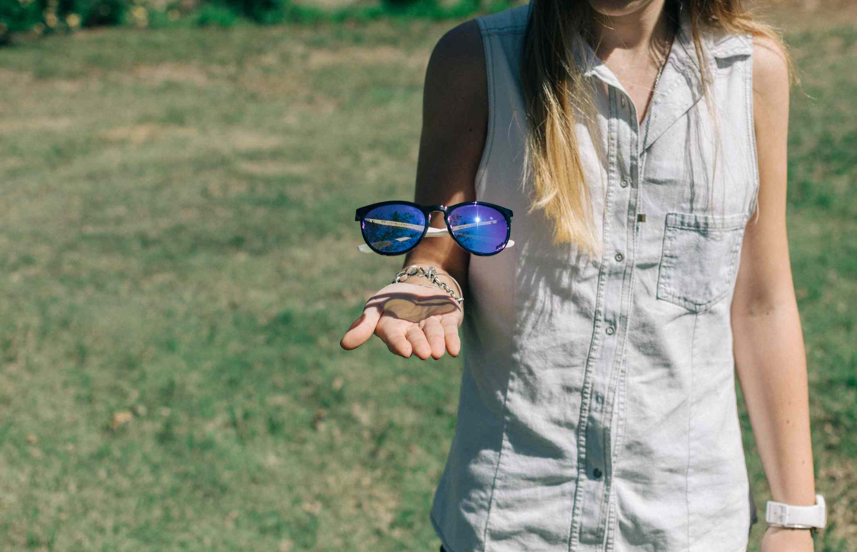 Woman makes sunglasses levitate above palm