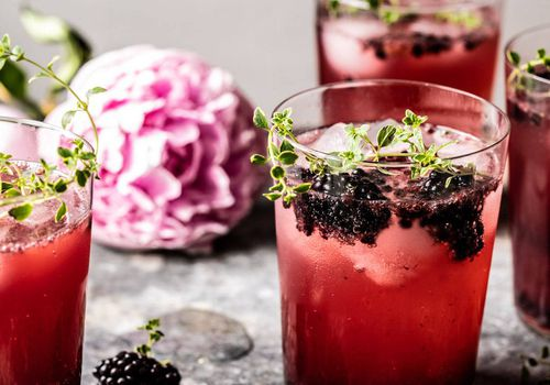 Blackberry and tequila cocktail garnished with fresh blackberries and thyme.