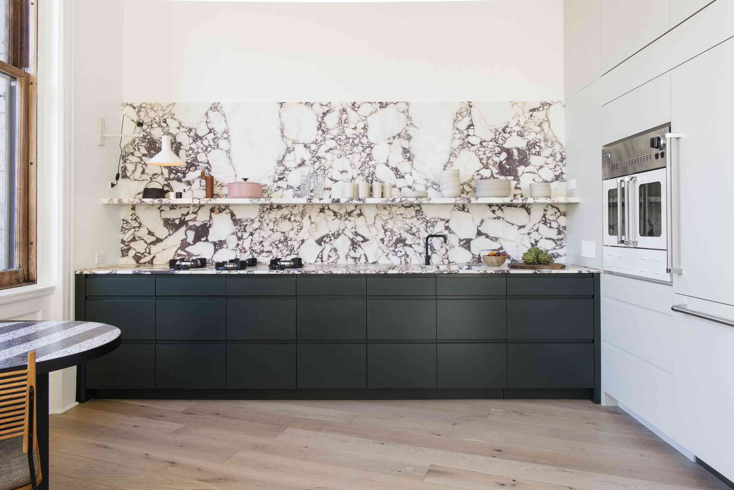 Minimalist kitchen with hunter green cabinetry, marble countertop and backsplash