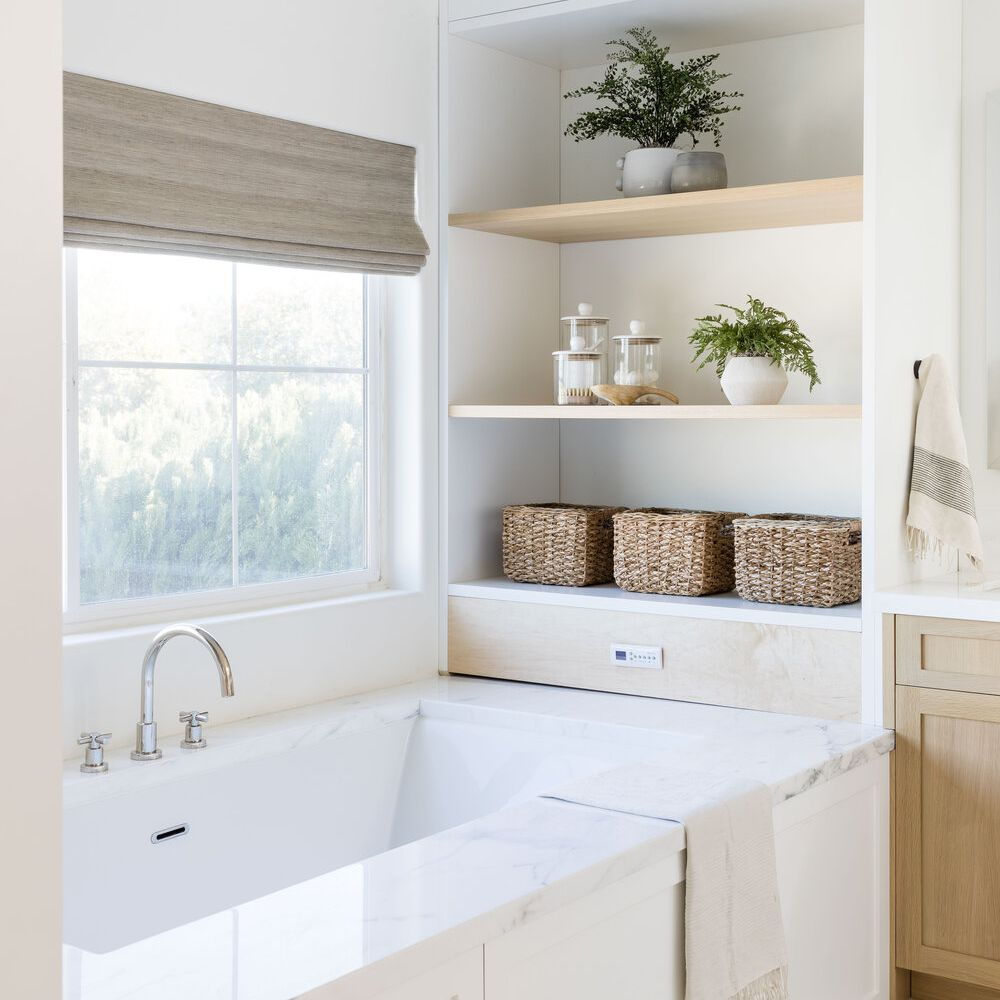 An all-white bathroom with built-in tubside shelves