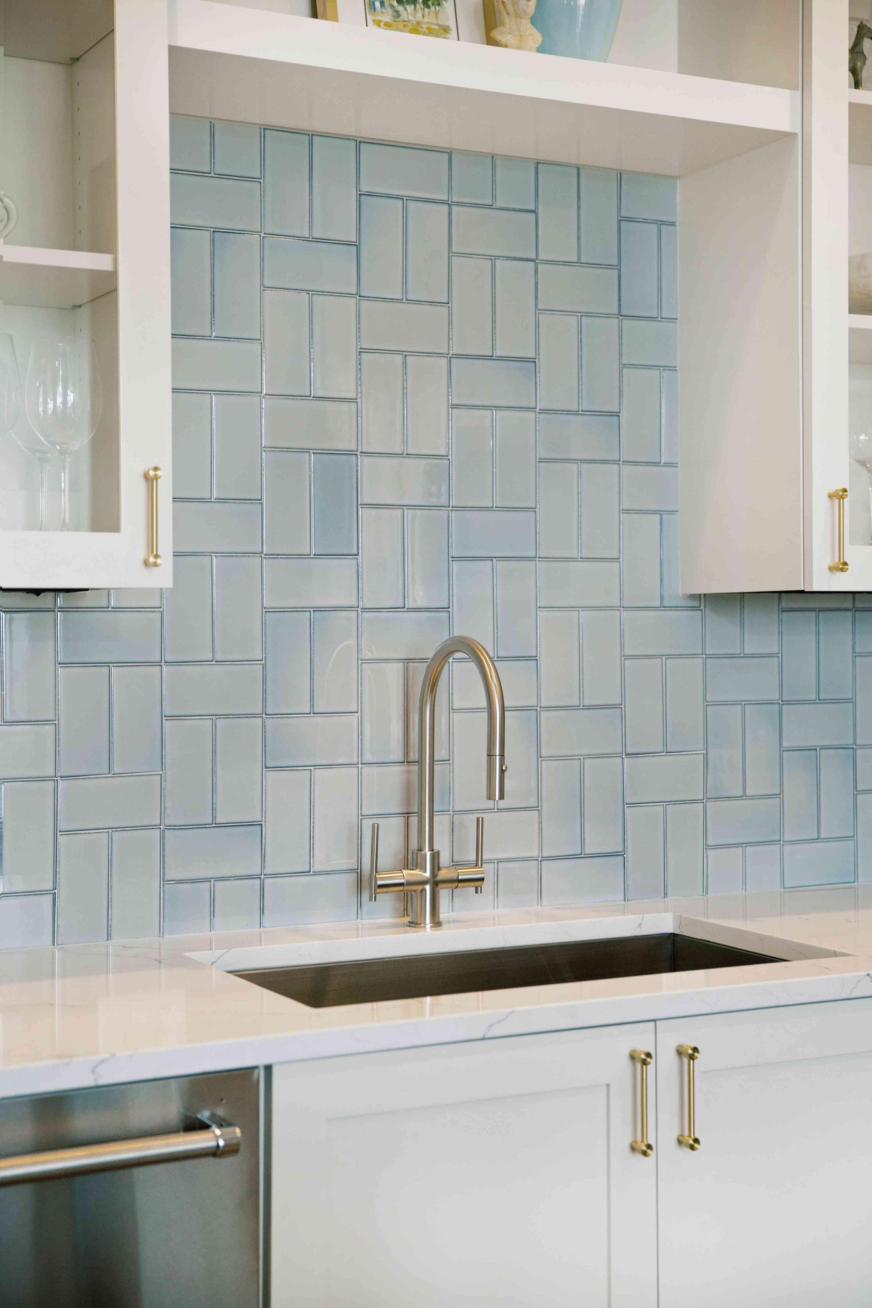 Close-up of kitchen sink and light blue backsplash behind it.