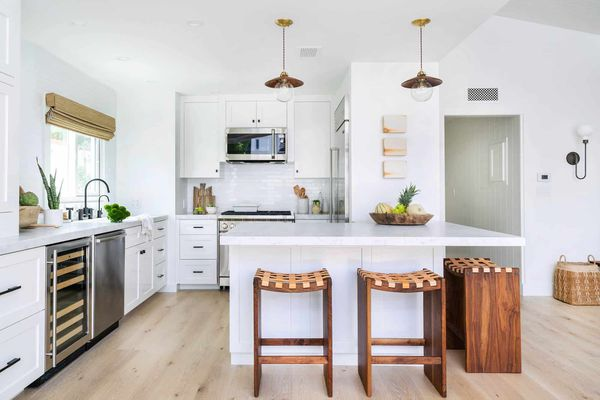 All-white kitchen with wooden bar stools and window treatment
