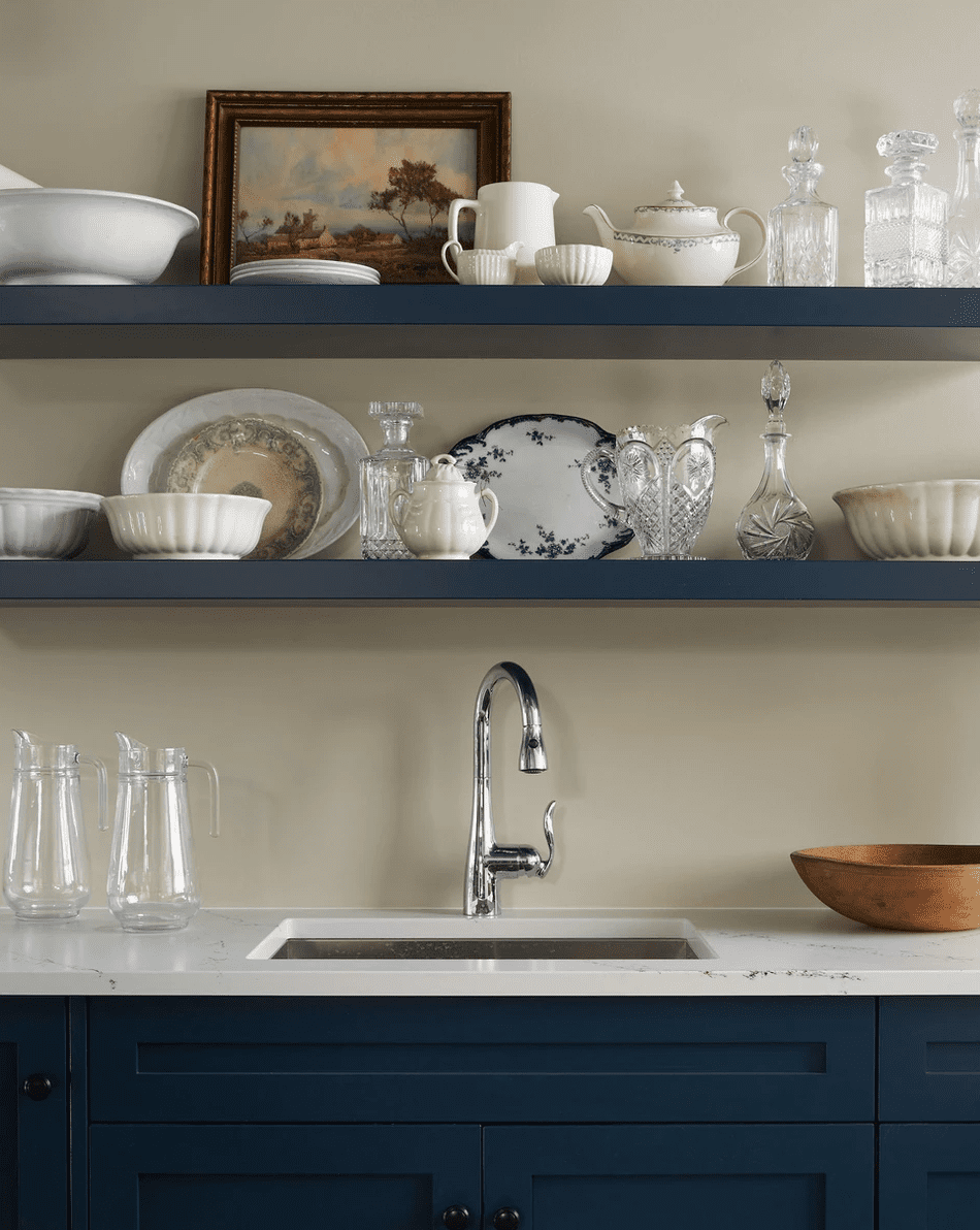 A kitchen with white countertops, blue shelves and cabinets, and off-white painted walls