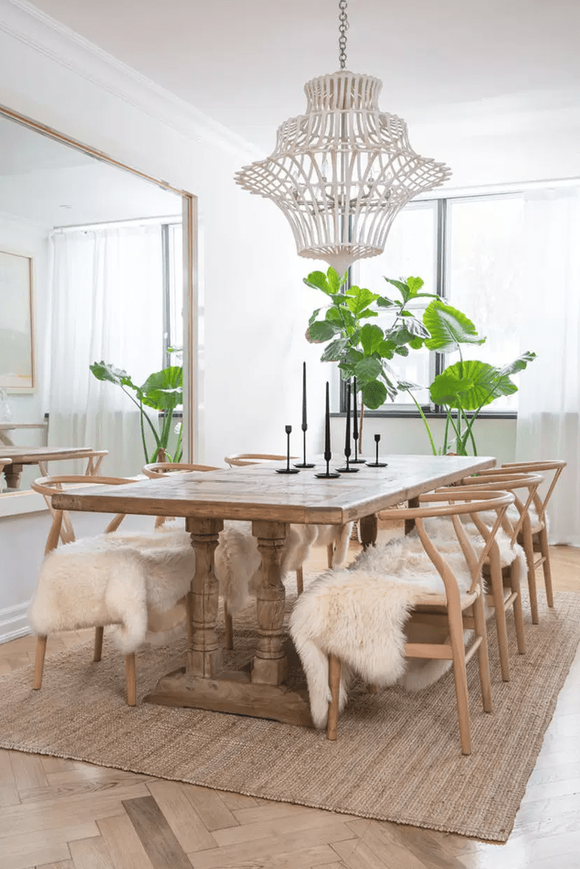 A dining room filled with wooden furniture that's been topped with fluffy white throws