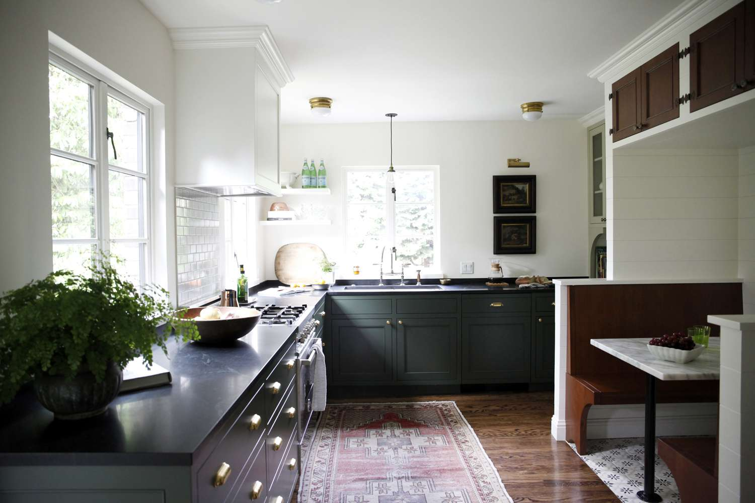 kitchen with dark green cabinets and plants