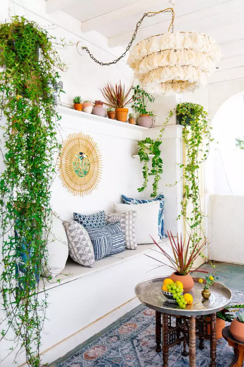 Bohemian living room with hanging plants and tasseled chandelier