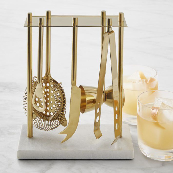 A rack holding gold-tone bar tools with a marble base and two cocktails beside it.