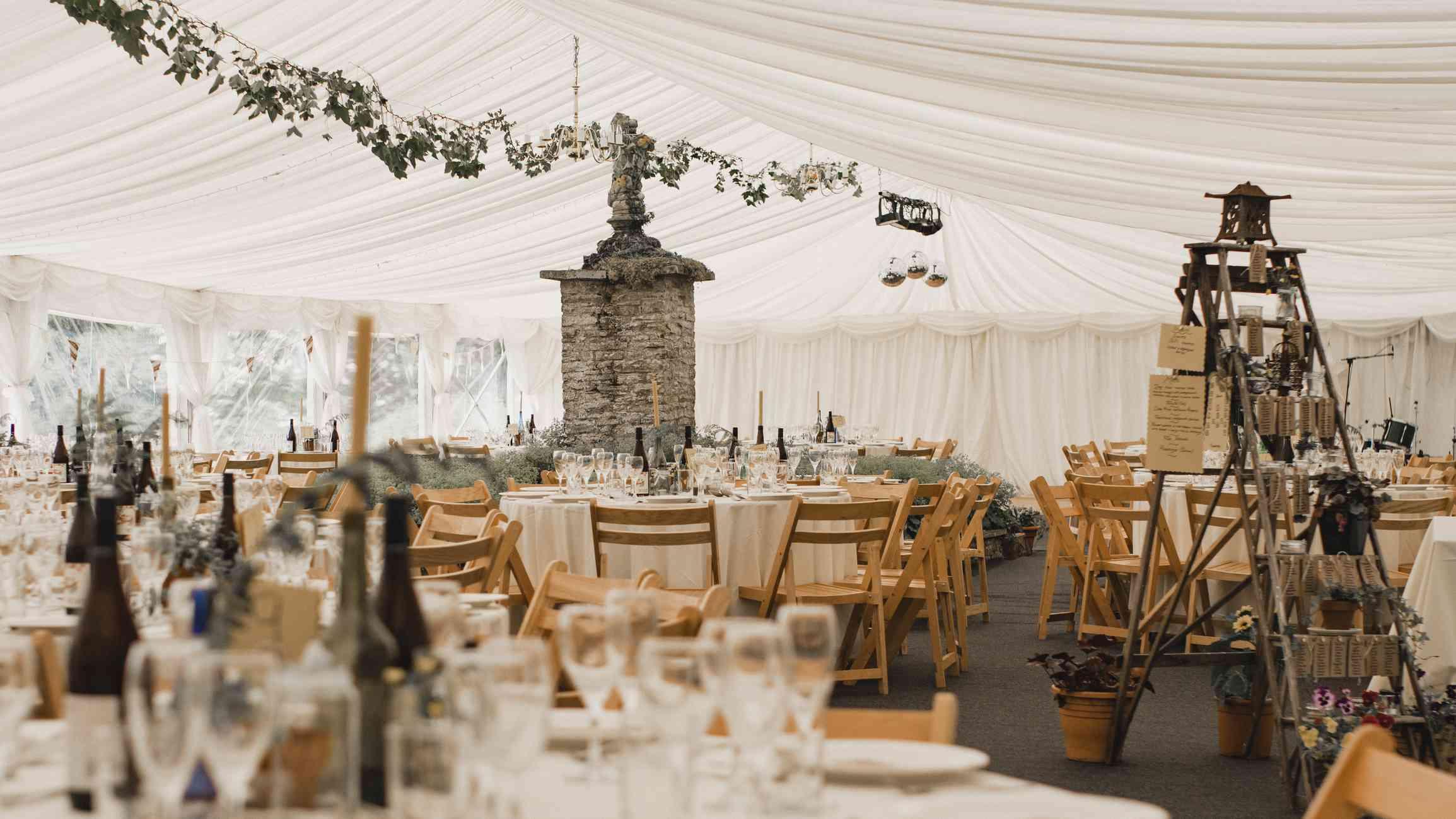 Wedding reception seating beneath tent