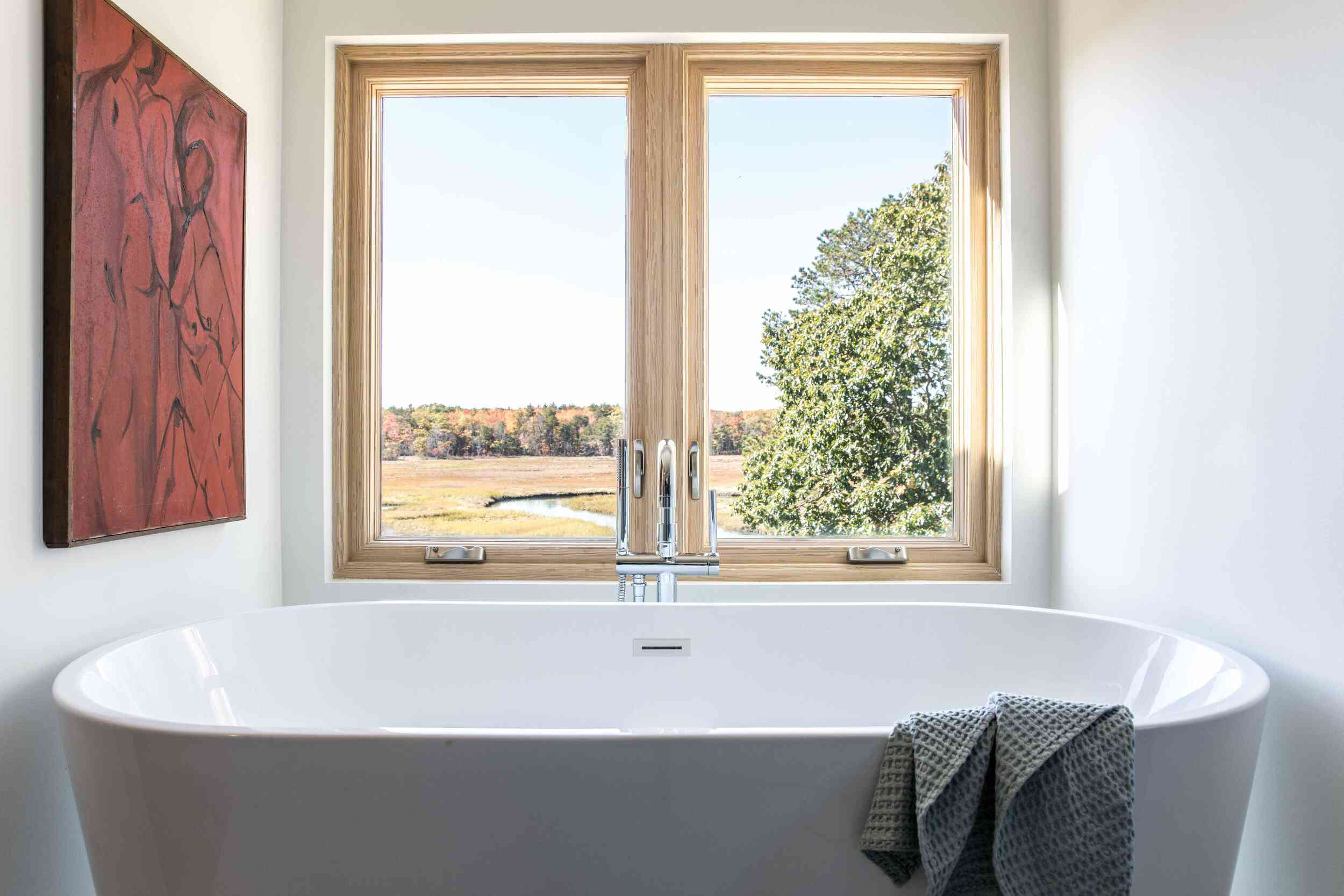 A small bathroom with a gray freestanding tub and a large red painting on the wall