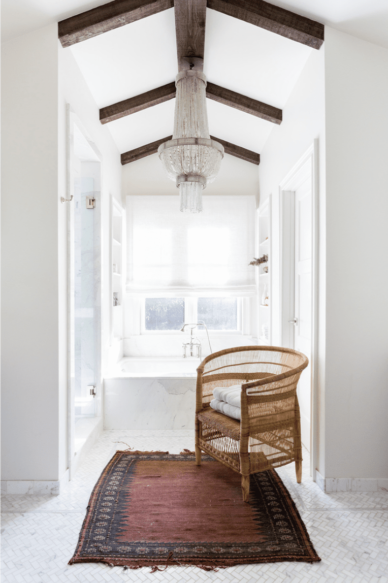 A small primary bathroom decorated with a chandelier, a woven chair, and a dark red rug