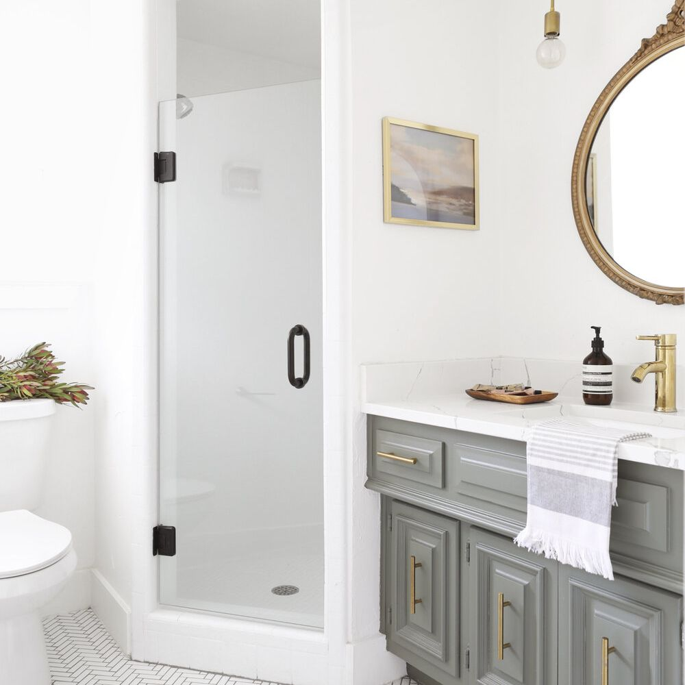 A bathroom with an ornate mirror in it