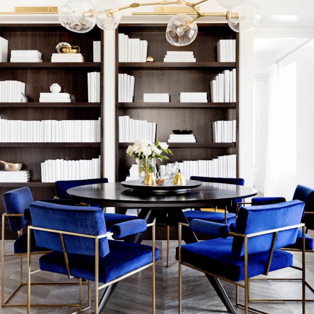 Masculine dining room with blue velvet chairs and bookshelves with white books