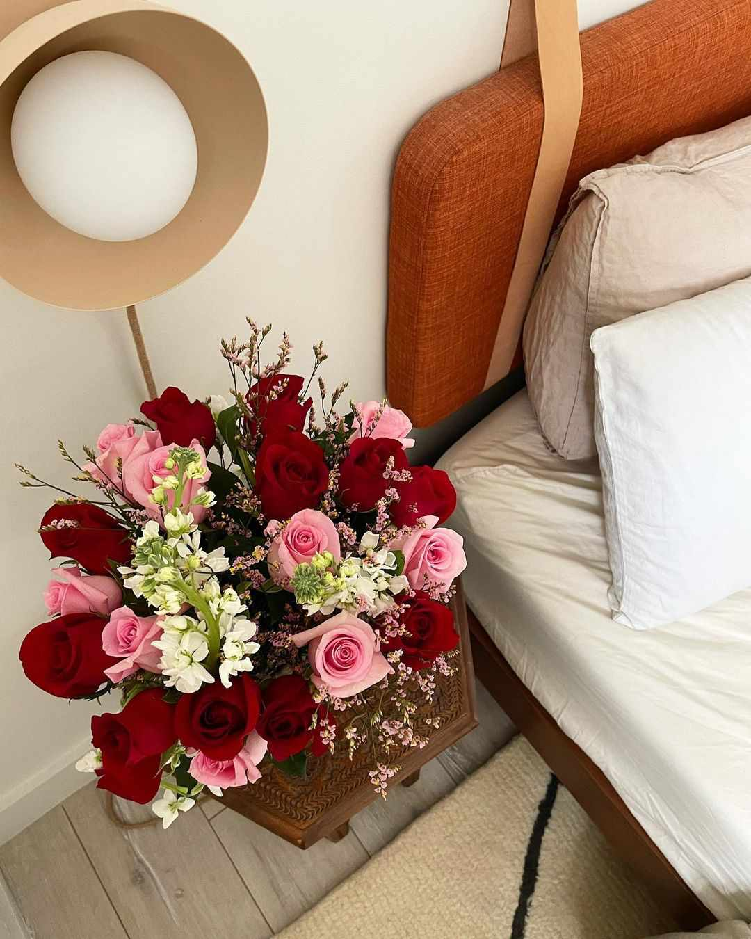 Bouquet of roses next to neutral bed.