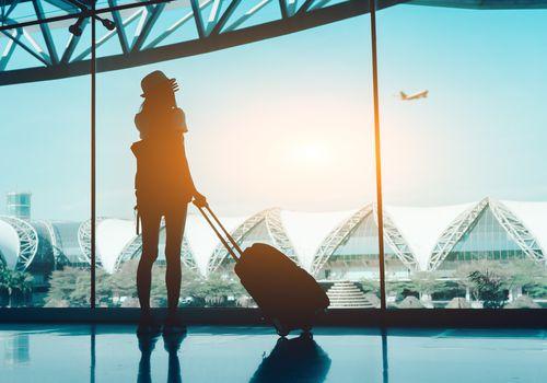 Mujer de pie con maleta en el aeropuerto