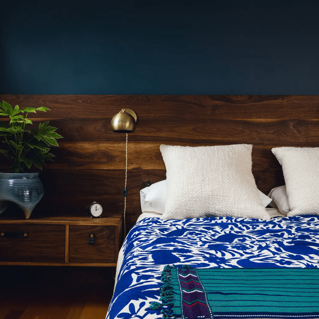 A bedroom with indigo walls, blue linens, and a teal and purple blanket