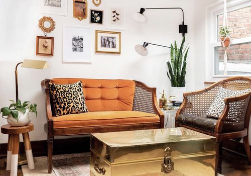 Eclectic living room with orange sofa, gold chest coffee table, and stool.
